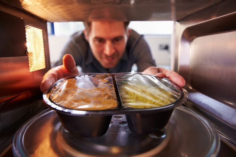 Man putting a meal into a mini microwave oven