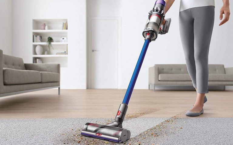 Woman using a Dyson stick vacuum to clean a dirty floor