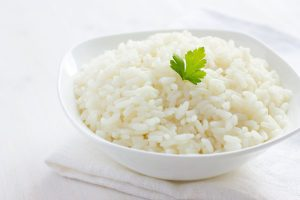 Cooked white rice with a parsley leaf on top served in a white bowl