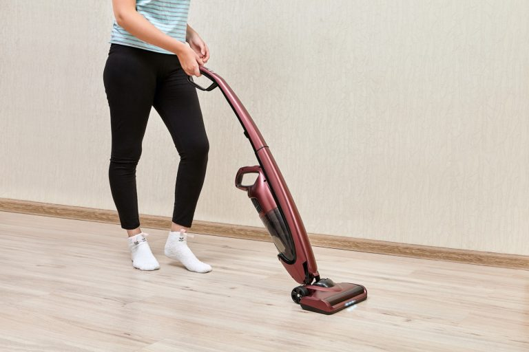 Woman cleaning a hardwood floor using a stick vacuum