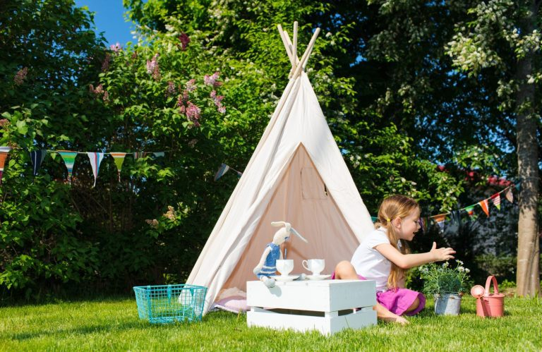 Girl playing with her teepee tent in a green backyard