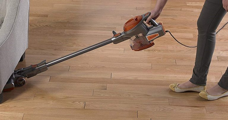 Vacuuming the floors with a corded stick vacuum