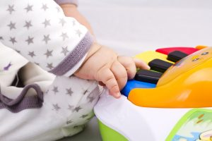 Baby playing on a piano attached to a play mat