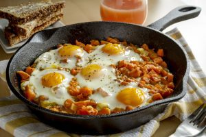 Delicious breakfast with eggs cooked in a cast iron skillet