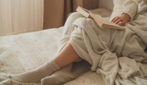 Woman reading a book while using a white weighted blanket