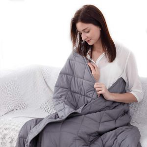Woman sitting in couch with a gray Esinfy weighted blanket