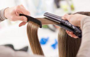 Straightening brown hair of a female customer