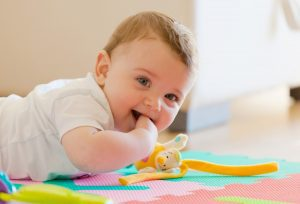 Smiling baby on a multi-colored play mat