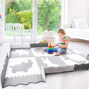Child playing on a white-gray Wee Giggles play mat