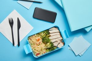 A blue box of hot lunch on a blue desk