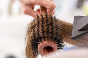 Combing damaged brown hair with a round brush