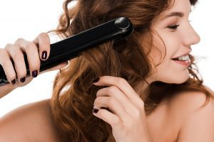 Brown haired woman curling her hair with a hair straightener