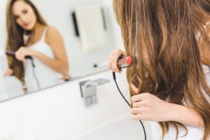 Brown haired woman straightening her hair in front of the mirror