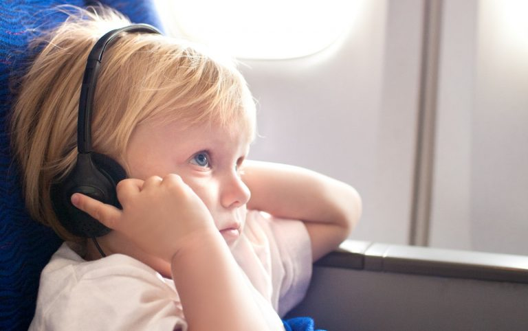 Kid wearing headphones on airplane