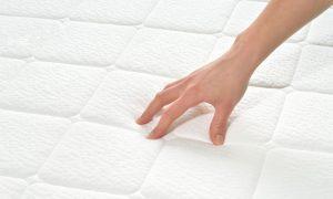 Hand touching a white mattress pad
