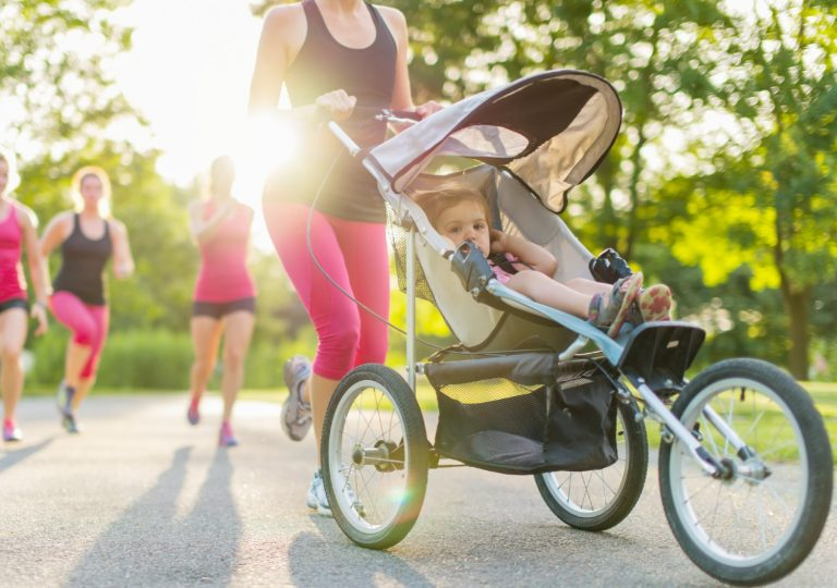 Group of women jogging with one pushing a jogging stroller in front of her