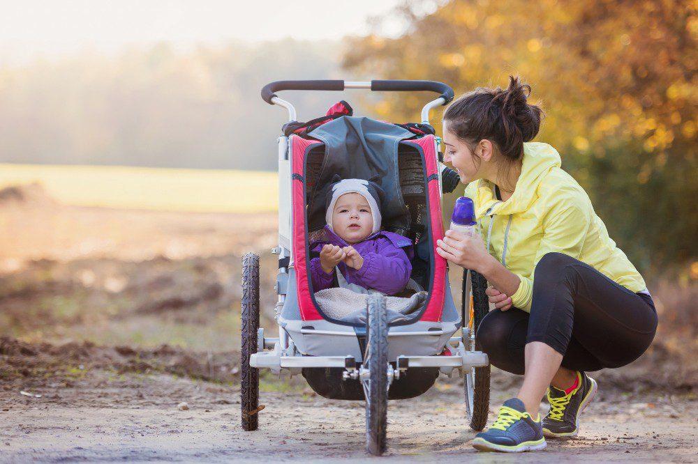 Mom taking a break from jogging and her baby sitting in a jogging stroller
