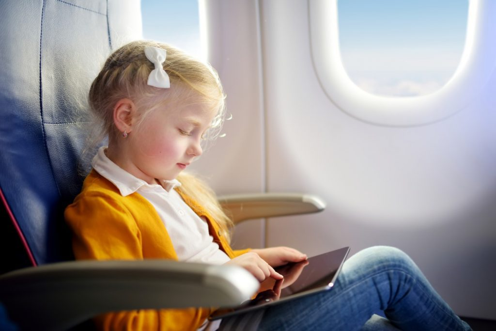 Girl playing games on tablet aboard an airplane