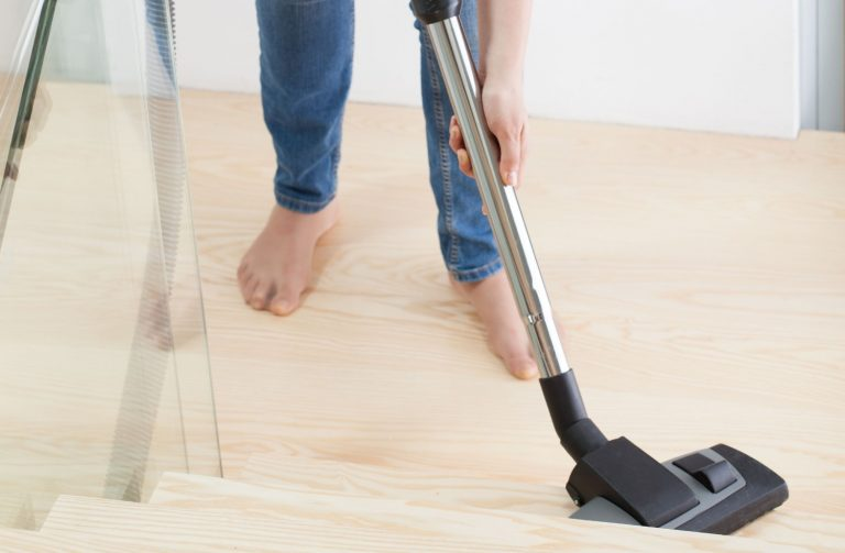 Woman vacuuming hardwood stairs