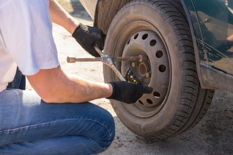 Man changing a tire using only a lug wrench
