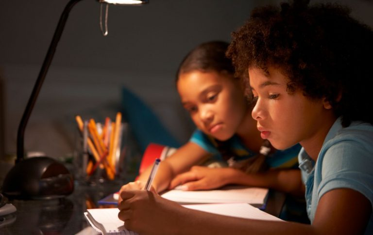 Kids studying under a desk lamp