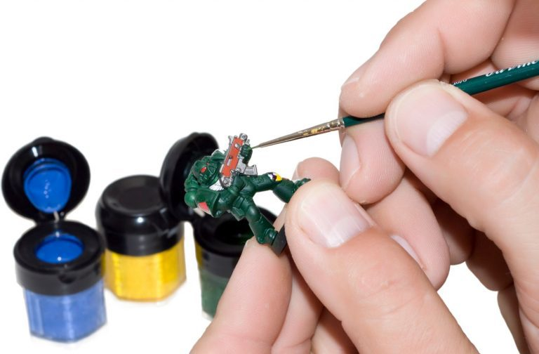 A set of hands holding a thin brush and a miniature while painting it