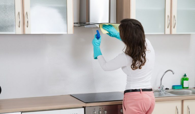 Woman cleaning grease from a range hood in her own kitchen