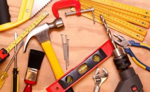 Collection of tools for home use on a wooden surface