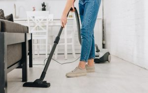 Woman cleaning a small apartment with a compact vacuum cleaner