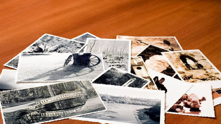 Pile of old photos on a wooden table