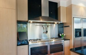 Contemporary kitchen with a large stainless steel wall mount range hood