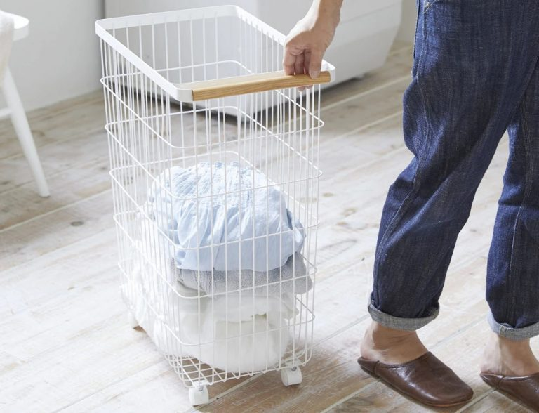 Woman pulling a white metal laundry basket half full of laundry