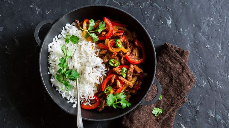 Meal with rice cooked and served in a cast iron wok