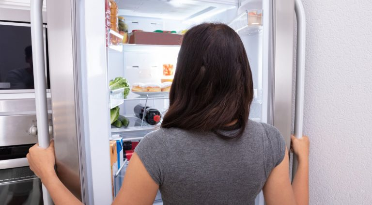 Woman opening a refrigerator and looking at the contents