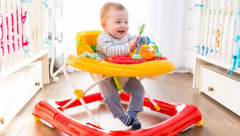 Happy baby in a red and yellow baby walker on hardwood floor