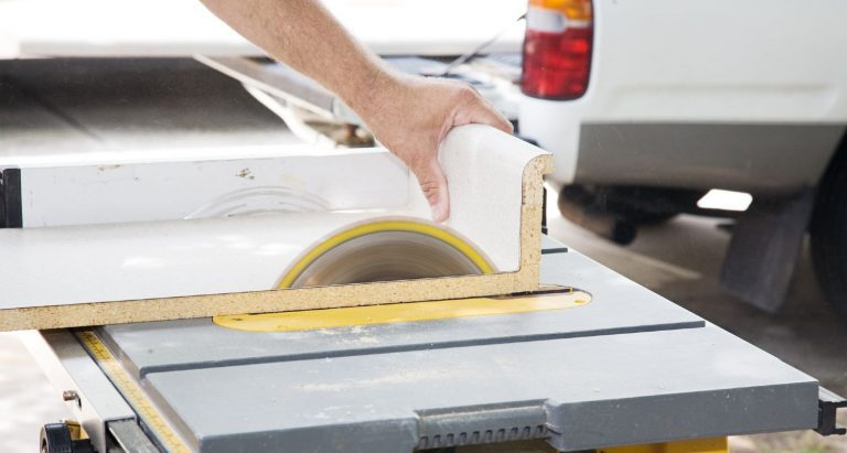 Contractor cutting wood panels on a portable table saw