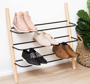 Eden & Co Wooden Shoe Rack leaned against a wall with black metal racks