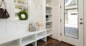 Well organized mudroom in bright colors, wooden flooring, and a glass door
