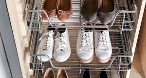 Shoes neatly stored on metal wire shelves inside a wooden cabinet