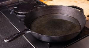 Seasoned cast iron skillet on a gas stove ready to cook