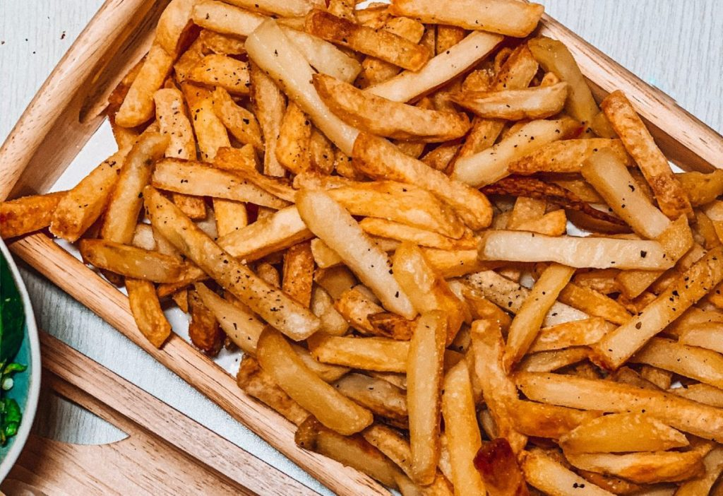 Crispy fries served in a wooden tray with salt and pepper sprinkled on top