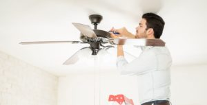 Technician mounting a ceiling fan with lights
