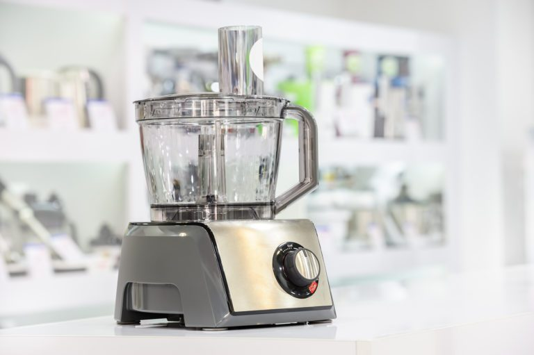 Food processor with a gray/silver finish on a white table