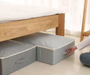 iWill Create Pro Under Bed Storage Container with a lid, sliding out from under a wooden bed