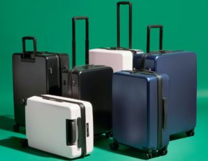 Different luggage standing in front of a green background