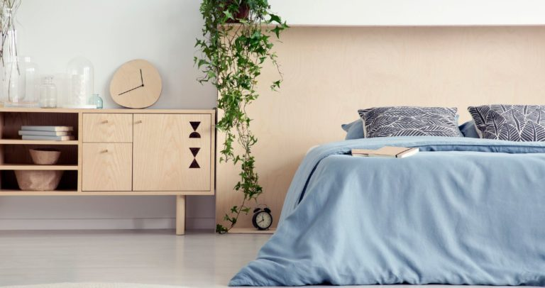 Neatly organized bedroom with a plywood headboard and blue linens