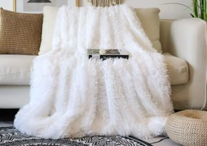 White faux fur throw blanket in a sofa with a book on top