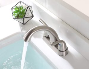 Brushed nickel faucet with the water running into a white sink