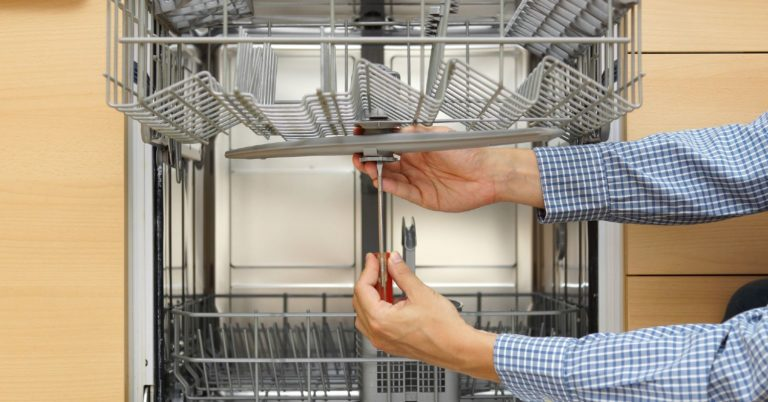 Professional repair technician inspecting and fixing the upper dishwasher arm