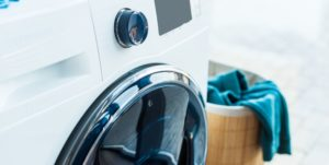 Front-loading washing machine in a modern look with a laundry basket in the background